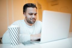 Young confident man with blue glasses using his laptop royalty free stock image