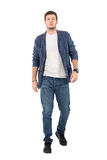 Young confident man in denim unbuttoned shirt and jeans walking towards camera. Full body length portrait isolated over white background Stock Photo