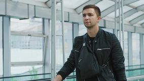 A young confident man with a handbag in modern airport terminal. Glass wall background. Travelling guy concept stock footage