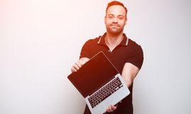 Young confident man holding laptop over white background. With sunlight effect.  royalty free stock photos