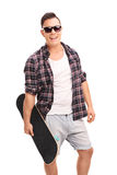 Young confident man holding a skateboard. Vertical shot of a young confident man holding a skateboard and looking at the camera isolated on white background Stock Photography