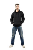 Young confident man in hood with hands in pocket looking at camera Stock Image