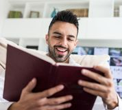 Young confident man reading book. At modern home Stock Image