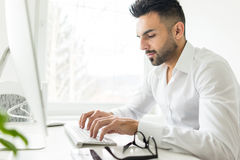 Young confident man working in modern office Stock Photography