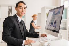 Analyst of online data. Young confident manager sitting by desk in front of monitor with financial charts stock photo