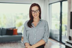 Young confident modern nerd woman posing in living room stock photos