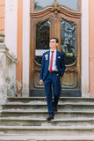 Young and confident newlywed groom posing in blue suit on old stairs at vintage building entrance Royalty Free Stock Photos