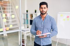 Manager in office. Young confident office worker with pen and notebook looking at camera on background of his workplace and whiteboard Royalty Free Stock Image