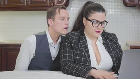 Portrait young confident plump woman working with laptop at the table. curious shy guy spies on the girl and the lady. Young confident plump woman working with stock video footage