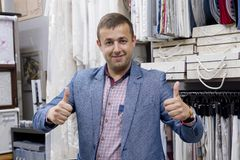 Young confident positive businessman fabric store owner showing thumbs up, gesture sign ok. Man standing in the store background royalty free stock image