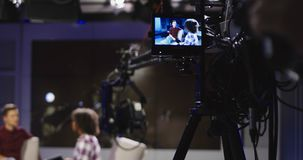 Masters of show in telecasting studio. Young confident and relaxed men and women taking participation in television show sitting in modern illuminated studio and Royalty Free Stock Photos