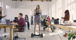 Young confident serious blonde business woman in dress riding electric gyroscooter in modern loft multiethnic office.