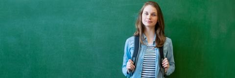 Young confident smiling female high school student standing in front of chalkboard in classroom, wearing a backpack.