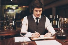 Young confident sommelier makes notes in notebook, tasting wine in restaurant. Wine tasting. Confident sommelier checks aging of wine Royalty Free Stock Photos