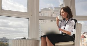 Young confident stylish business woman working on laptop at modern office, drinking coffee and looking at big city.  stock footage