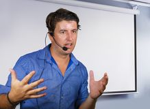 Successful man working as motivational speaker and business management coach talking to audience in conference room using headset. Young confident and successful royalty free stock photos