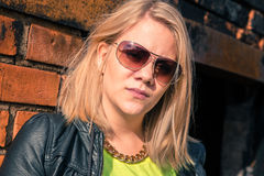 Young confident woman with blonde hair standing against a brick Royalty Free Stock Image