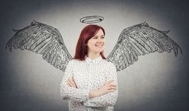 An angel dream. Young confident woman smiling with crossed hands dreaming imagining her as an angel with wings sketch behind her back and a halo above head stock images
