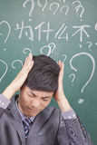 Young confused businessman in front of blackboard Royalty Free Stock Images