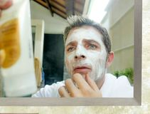 Young confused Caucasian man at home reading instructions of white facemask product while applying the facial mask on his face. Close up face portrait of young stock photography