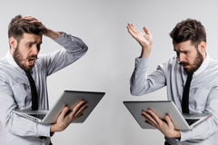 The young confused and frustrated man with his laptop computer Stock Photos