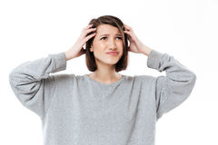Young confused woman keeping her hands on head. Portrait of a young confused woman keeping her hands on head isolated over white background Stock Photos