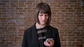 Young confused woman looking at phone with disappointed expression, isolated on brick background stock footage