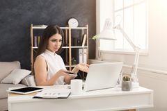 Young confused woman working on laptop. Young confused woman sitting at the table and working on laptop and having some troubles , copy space Stock Photography
