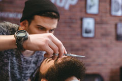 Young consentrated barber grooming beard of man with scissors stock photo