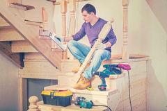 A young construction contractor sitting on steps of wooden ladde Royalty Free Stock Photo