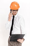Young construction engineer in orange helmet with folder talking on phone on white background Stock Photography