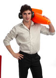 Young construction foreman with traffic cone. Young, handsome construction foreman with rolled-up sleeves, wearing hearing protection and carrying a traffic cone Stock Image