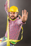 Young construction man with hard hat wearing a fall protection. Harness and lanyard for work at heights saluting.Gray background royalty free stock images