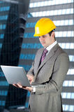 Young construction worker contractor. Young construction worker contractor using notebook in front of modern corporate building. Isolated. Clipping path Royalty Free Stock Image
