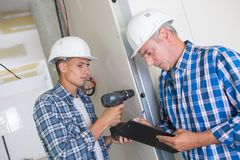 Young construction worker drilling hole repair in house Royalty Free Stock Photos
