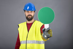 Young construction worker with hardhat holding a green traffic s. Ign over gray background Royalty Free Stock Photos