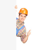 Young construction worker with helmet posing behind a panel and Royalty Free Stock Images