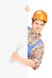 Young construction worker with helmet posing behind a panel and. Holding wrench isolated on white background Stock Photography