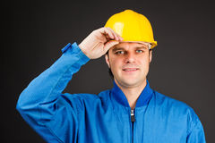 Young construction worker with his hand on hard hat brim Royalty Free Stock Photos