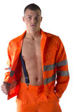 Young construction worker with orange suit open on naked torso Stock Photography