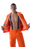 Young construction worker with orange suit open on naked torso Stock Images