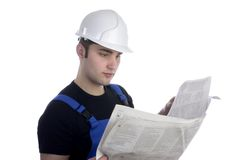 Young construction worker studying newspaper for jobs Stock Photo