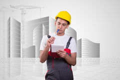 The young construction worker taking notes. Young construction worker taking notes Royalty Free Stock Photo