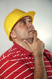 Young construction worker thinking Royalty Free Stock Photos