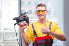 The young construction worker in yellow coveralls Stock Photography