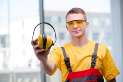 The young construction worker in yellow coveralls. Young construction worker in yellow coveralls royalty free stock image