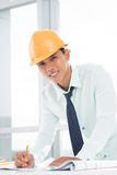 Young constructor. Vertical portrait of a cheerful young constructor being at his workplace Stock Photos