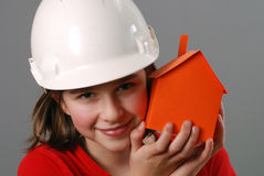 Young constructor. Teenager with orange paper house model stock image