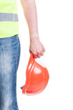 Young constructor hand holding a safety hardhat. Young construtor hand holding a safety hardhat as work equipment isolated on white background Stock Photo