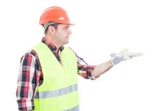Young constructor showing something on open palm. With empty copy space isolated on white background Stock Photography